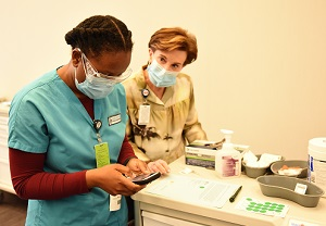 Jeanette looks on as a nursing student in scrubs enters data on a handheld device