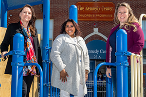 Three women leading the program, from RSM, IHP and Kennedy Center, stand atop a blue and yellow jungle gym outside the kennedy cetner
