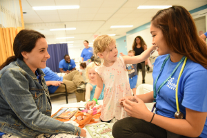 Nursing students Sophia Nedelman (left) and Kristin Nioko help a young girl and her doll at the Teddy Bear Clinic.