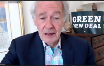 """screen grab of sen markey talking with a """"green new deal"""" sign behind him"""