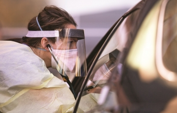 Shelby Lee Freed wears a face shield as she talks to someone through the window of a car