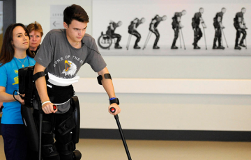Photo of paralyzed teen working with Andrea Coiro, DPT '14,  at Spaulding Rehabilitation Hospital Spinal Cord Unit