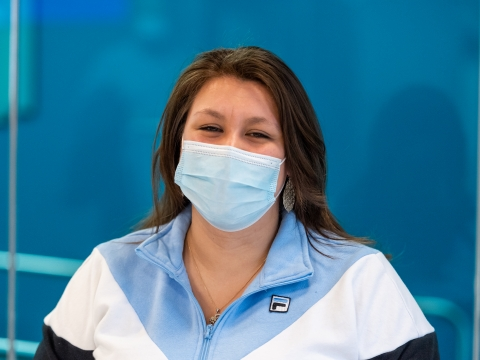 Photo shows a female PT student with a blue surgical mask and smiling eyes