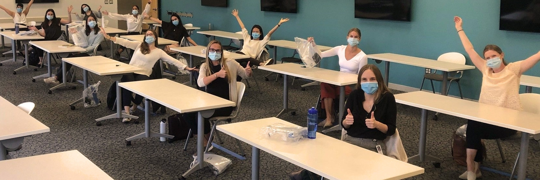 Students socialy distanced in a classroom with masks wave to the camera