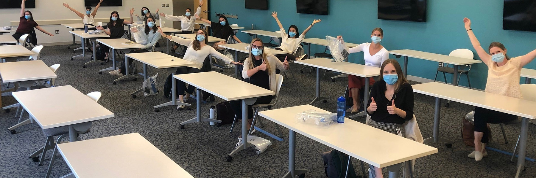 students at spaced out desks in a classroom wear masks and give thumbs up