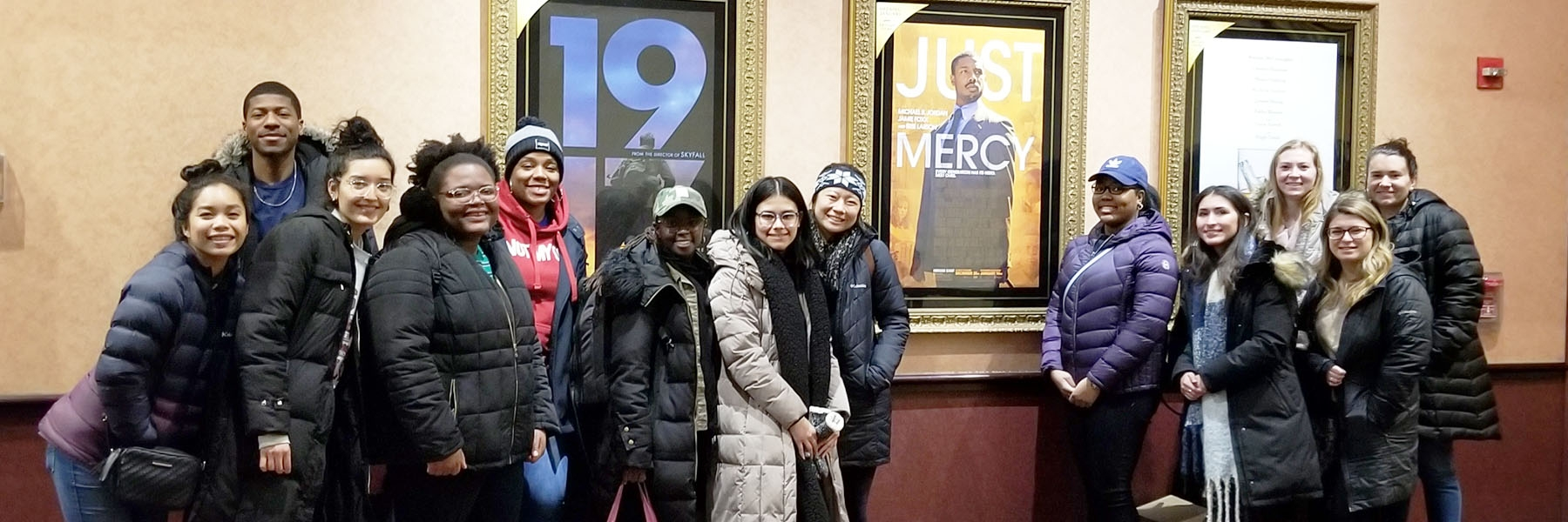 Photo shows group of students at theater in front of Just Mercy movie poster