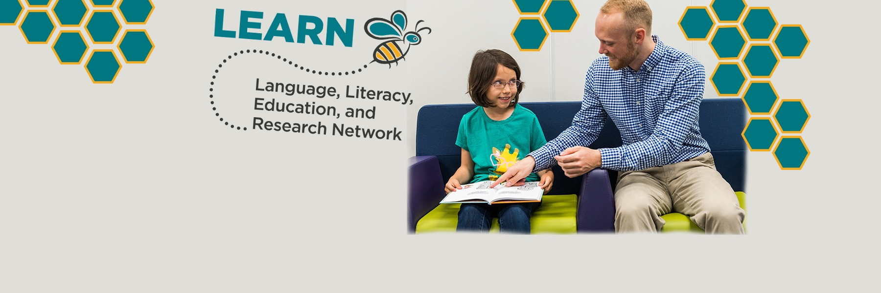 Man reads to little girl on a couch with LEARN logo on wall - it is a bee with honeycombs