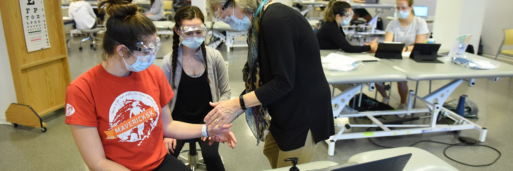 Professor assists two sitting female students who are working on arm movement. They all wear facemasks and goggles.