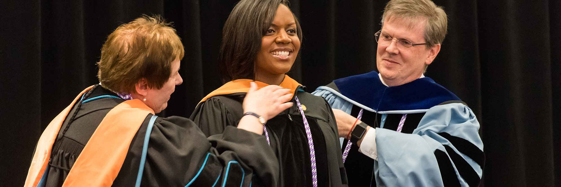 smiling graduate in gown receives honors