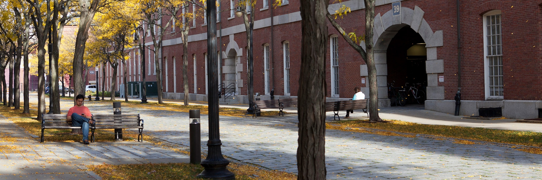 Historic Charlestown in the fall shows a man on a bench under yellow foliage