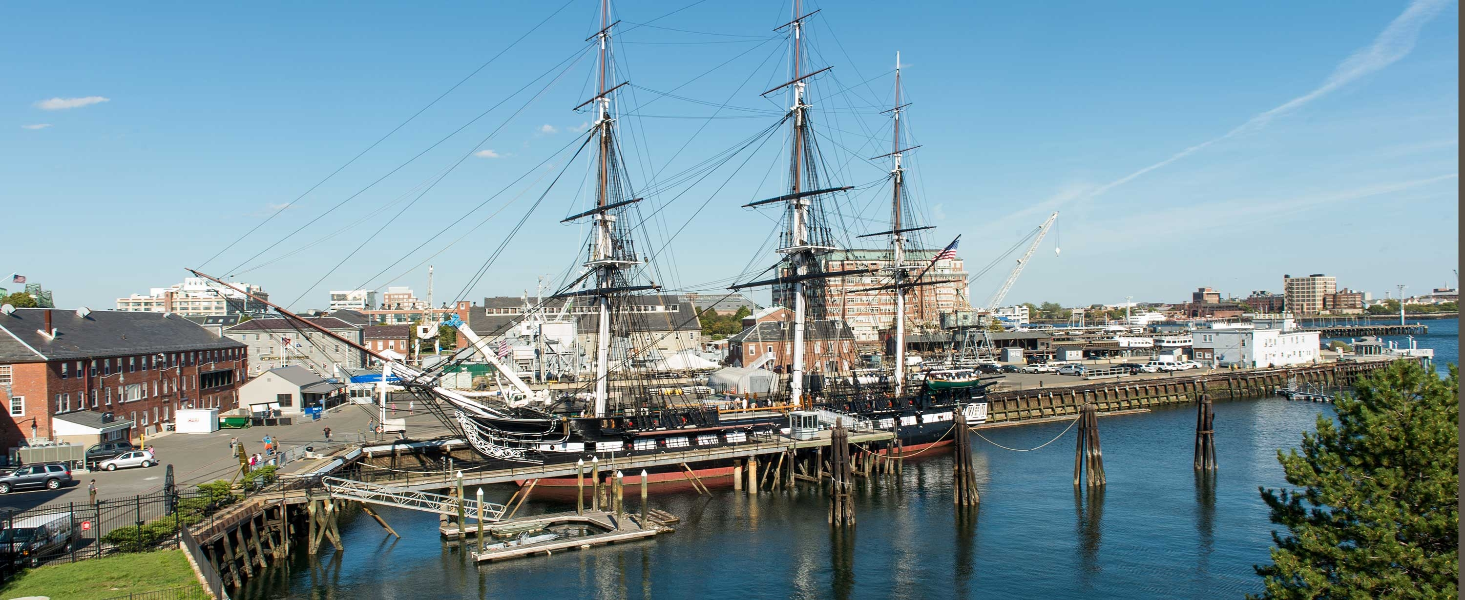 Photo of the U.S.S. Constitution in the Charlestown Navy Yard with Boston in the background