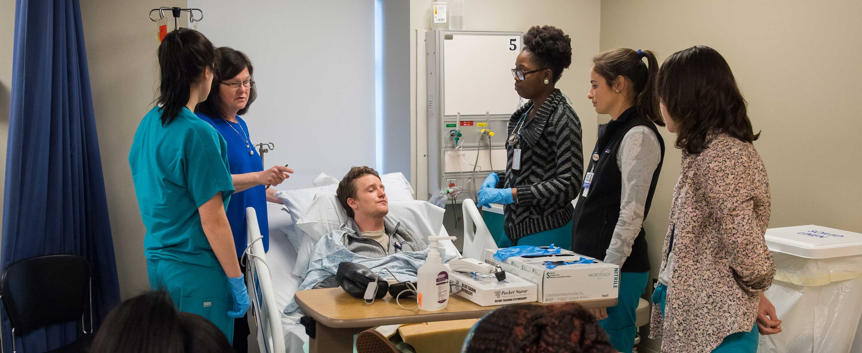 Image of students working with a simulated participant at the MGH Institute