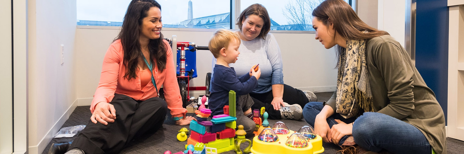 OT students sit with a child on the floor as he plays with toys