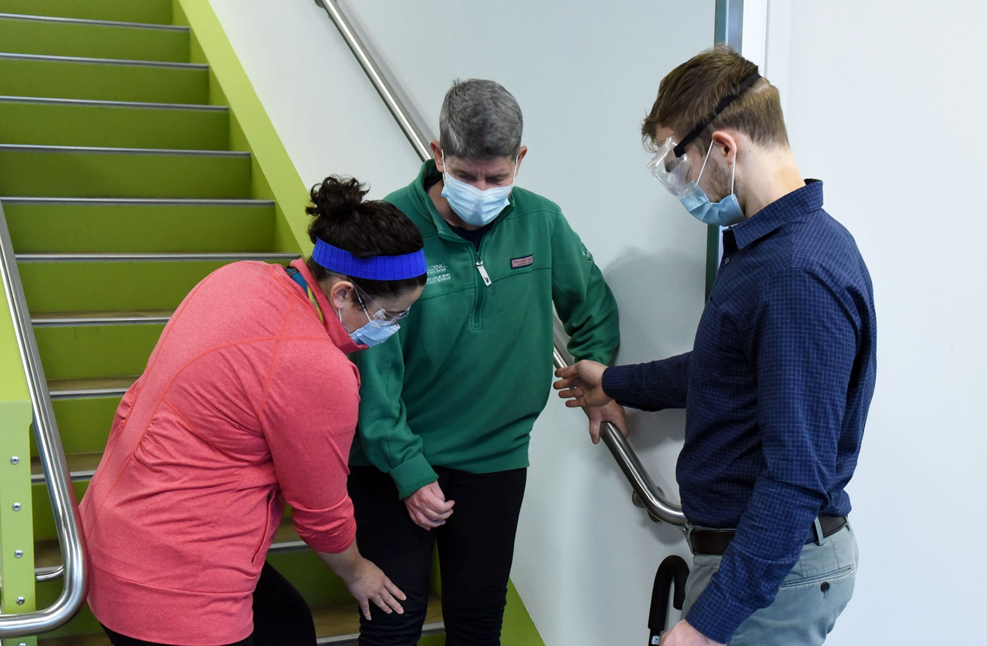 male and female student help man down stairs; all wear facemasks