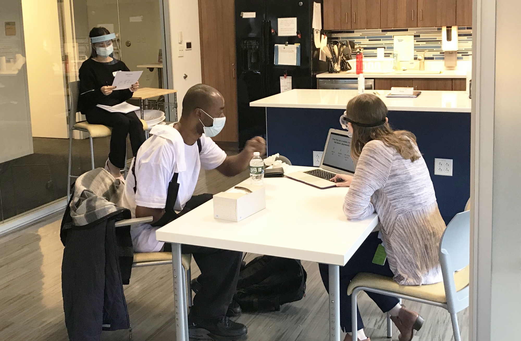 patient and OT student sitting at a table in the IMPACT center kitchen, both wear masks
