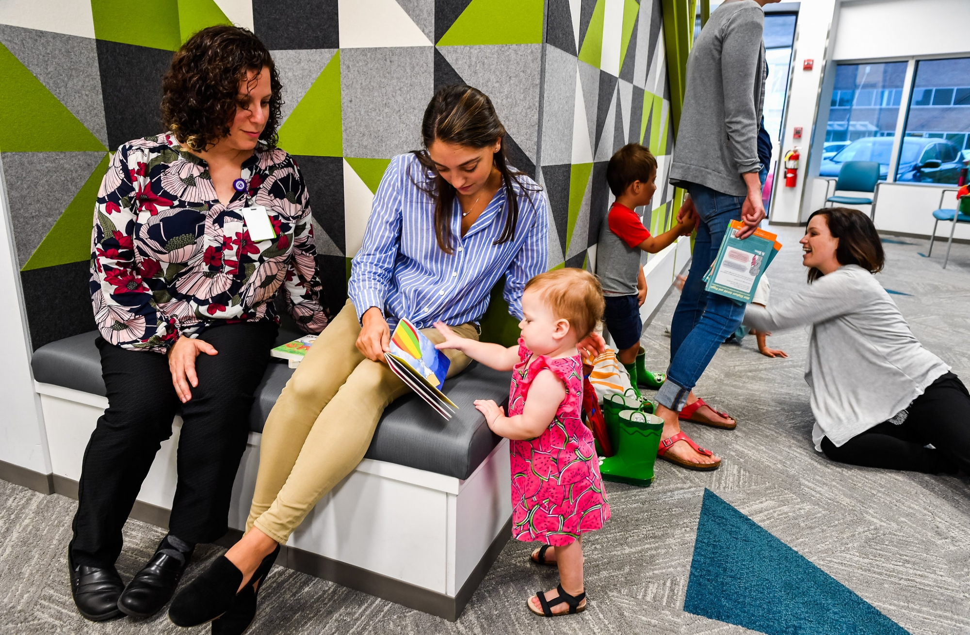 Student reading to a toddler in the lab play area