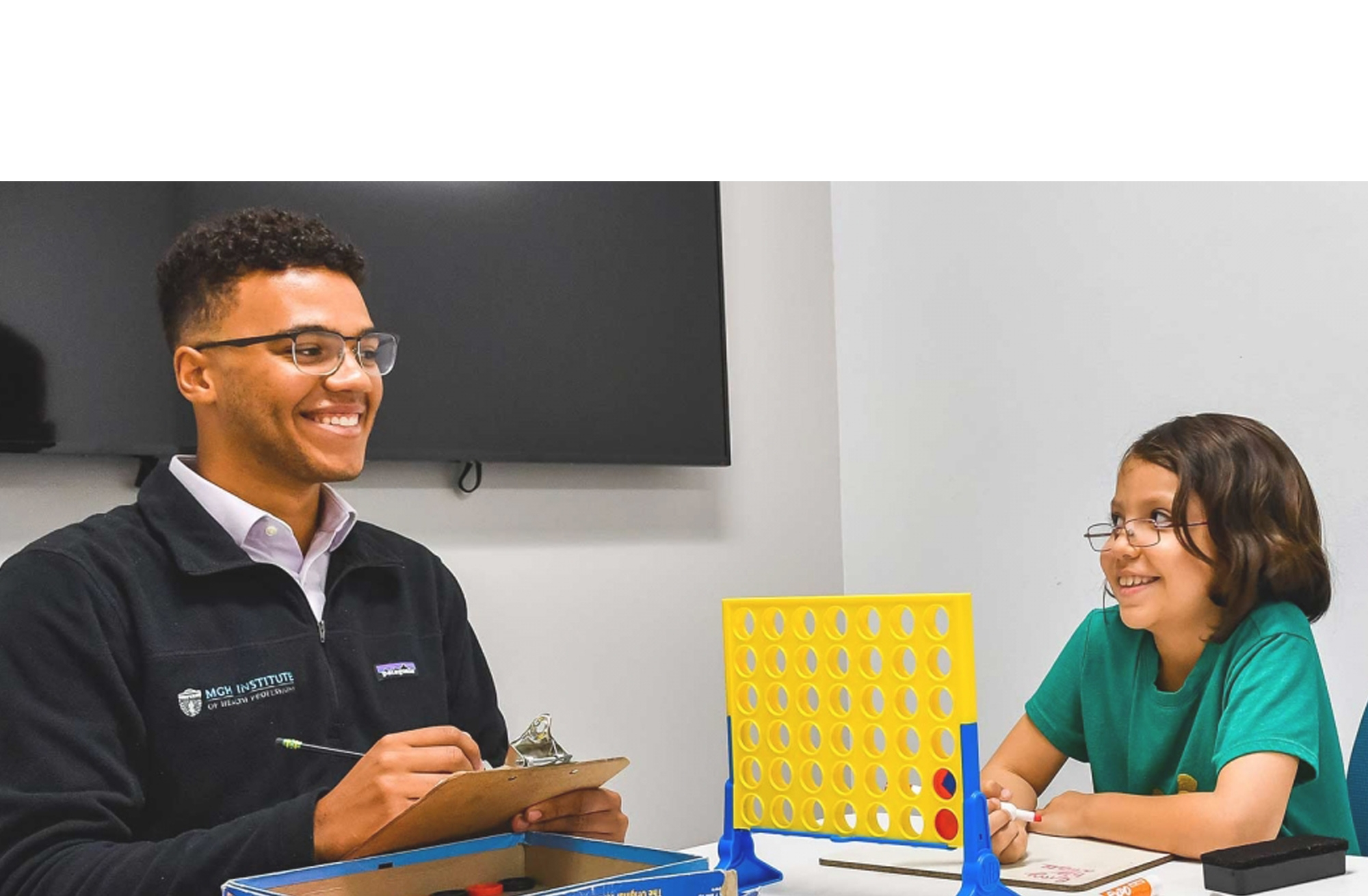 A male student smiles at a table and takes notes in a clipboard as a child client plays connect four