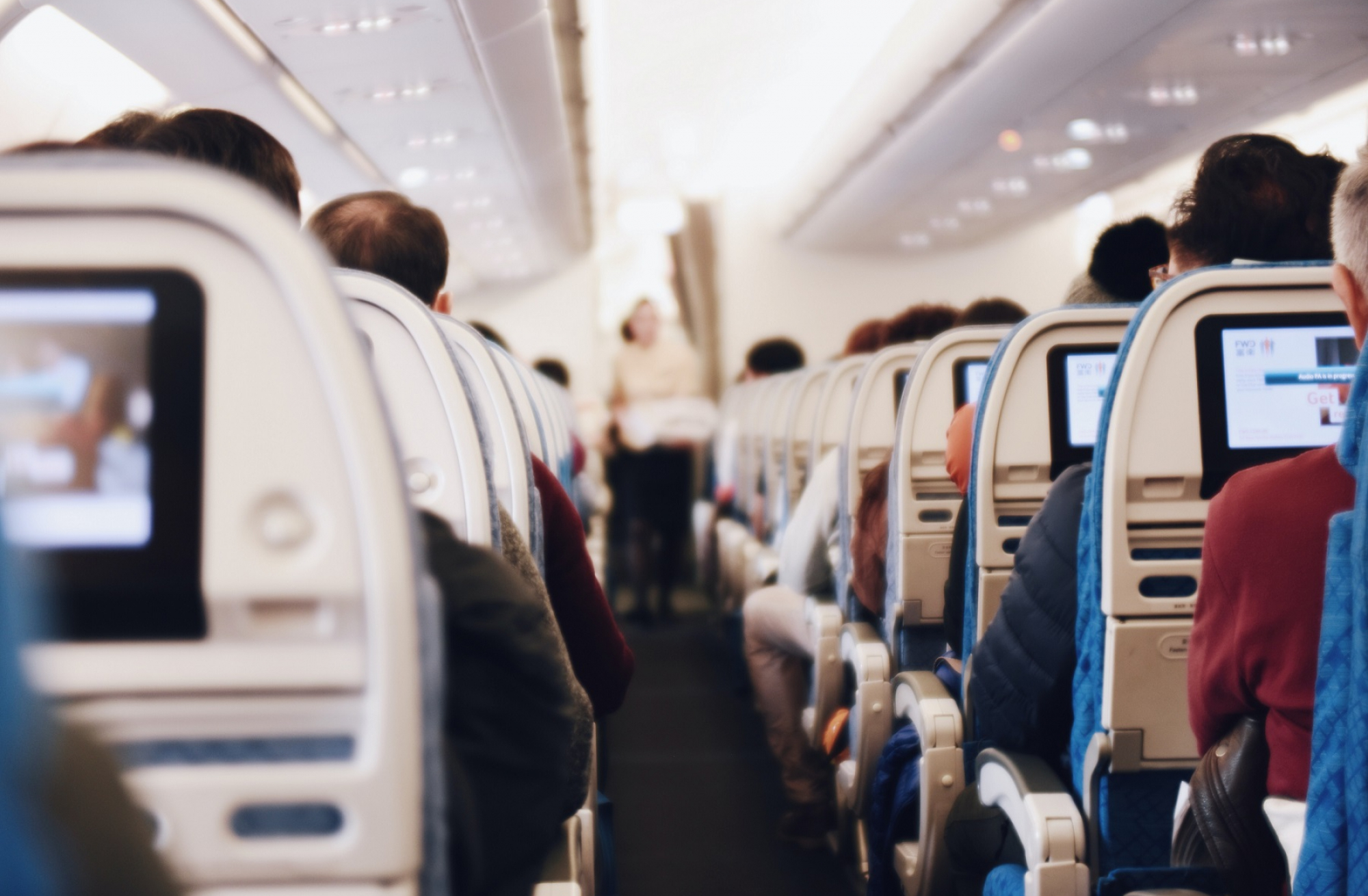 photo shows airplane aisle from the back with rows of seats