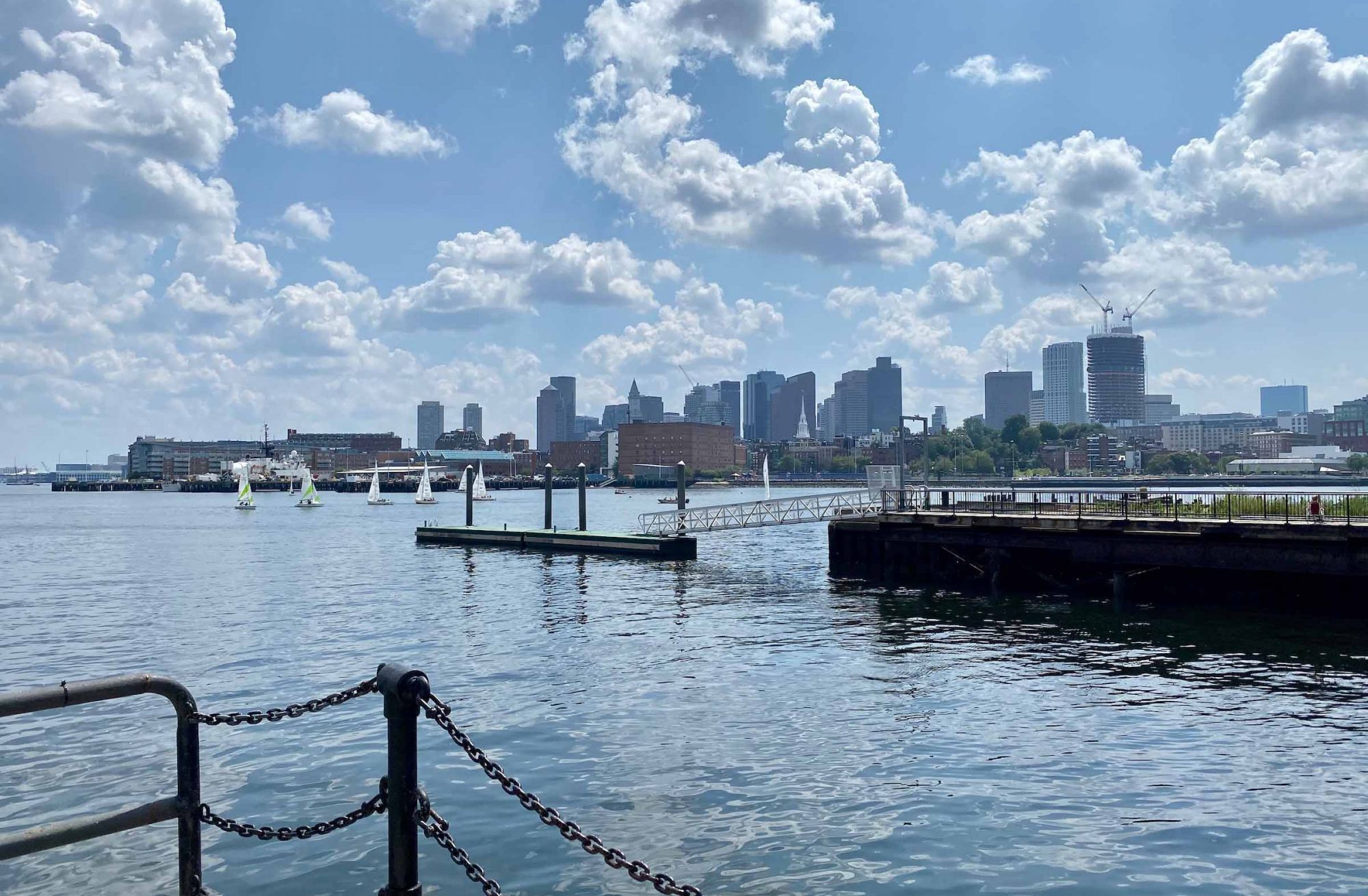 skyline view of boston from pier in navy yard shows sailboats and blue sky