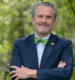 Ken stands under a tree, arms folded, with a blue blazer and green bow tie