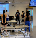 DPT students, adhering to social distancing standards, watch Associate Professor Doug Gross as he works with the other half of the class in an adjacent room.