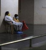Patients sit with masks on