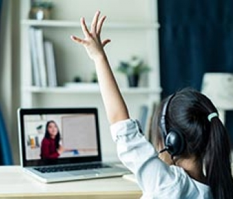 child raising hand while learning remotely