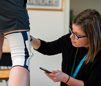 image of Physical Therapist examining a knee in a brace