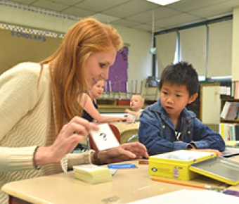 Photo of teacher with student working on reading in the classroom