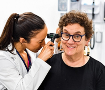 Image of nursing student giving an ear exam to a standardized patient