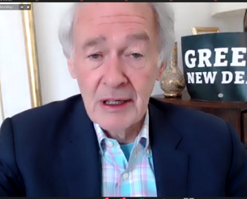 "screen grab of sen markey talking with a ""green new deal"" sign behind him"
