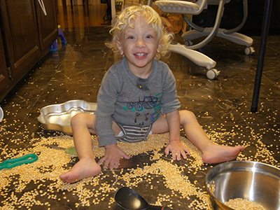 Amit on the kitchen floor in a pile of corn kernels