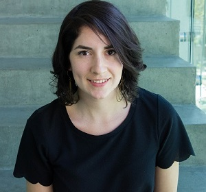 photo of Rosa in front of a concrete staircase, she has short dark hair and a black short sleeved top