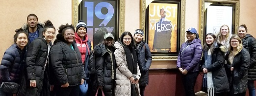 Students in front of just mercy poster