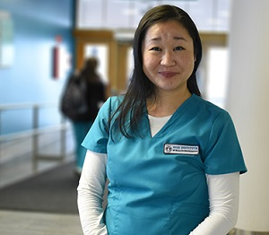 Photo of Kanayo in a hallway at the IHP, she wears a blue scrub top