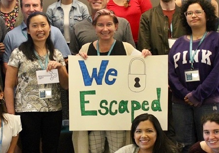 "Photo of group with ""we escaped"" sign"