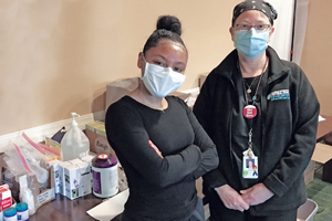 NP student Jordana Dalila Baez and nursing faculty Antonia Makosky in front of a table of medical supplies. They both wear masks