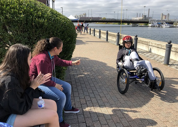 Photo shows a wheelchair race with family cheering on participants