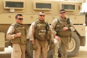 Tom Doucette (far right) with his Iraq team members in front of the truck that hit an IED bomb.