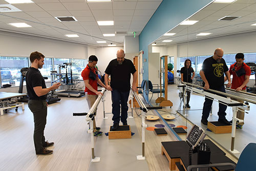 Photo of DPT students working with client in the Adult Rehab Gym in the IMPACT Practice Center