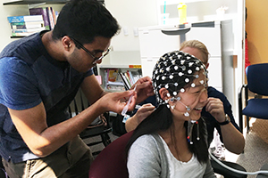 An undergraduate intern practices EEG net application