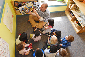 Photo of man reading to a group of young children
