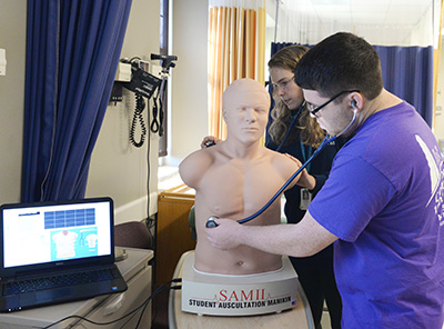 Physician Assistant Studies students listen to heart and lungs of a manikin
