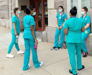 female nursing students stand in a circle talking wearing face masks