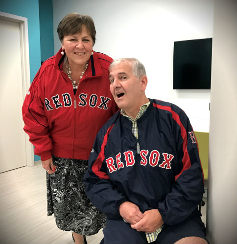 Aphasia center member with red Red Sox Jacket standing and smiling alongside second Aphasia center member sitting and smiling with dark blue Red Sox Jacket in community room at IPC